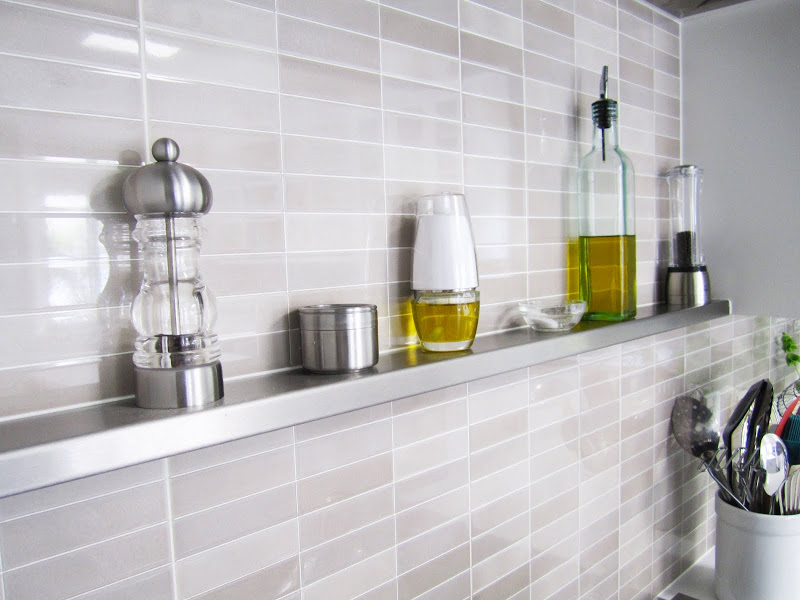 Kitchen with tile backsplash behind the stove and a small stainless steel floating shelf perfect for oils and spices