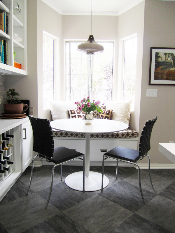 Breakfast nook with banquette seating, a pendant light and a round white table