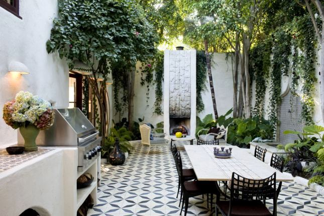 Outdoor courtyard with tile floor, grand modern silver fountain, a lounge area and dining room