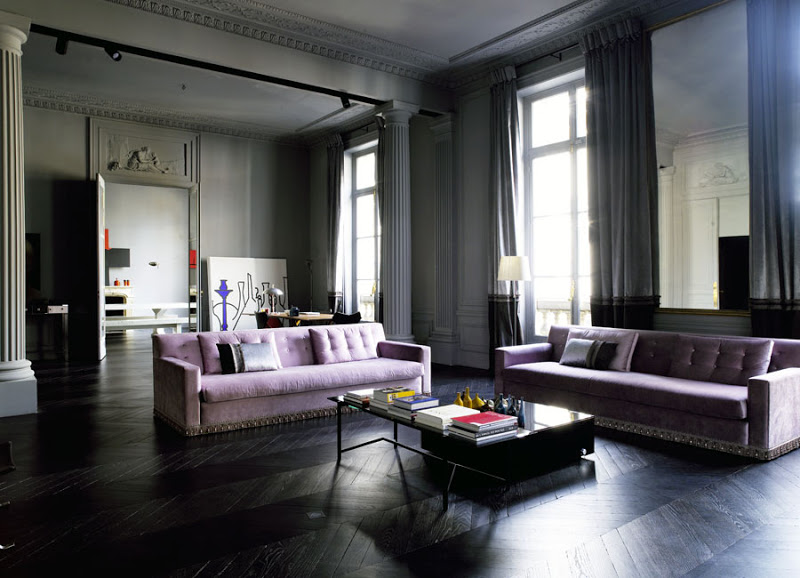 Dark grey living room with dark herringbone wood floor, purple sofas, and columns