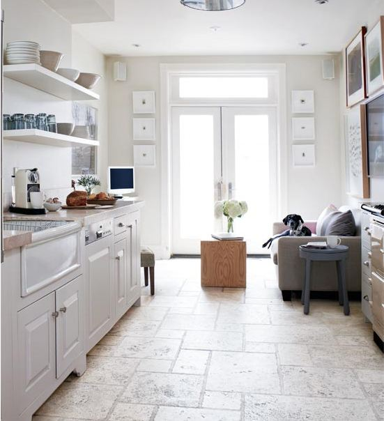 Bright gallery kitchen with stone tile floor