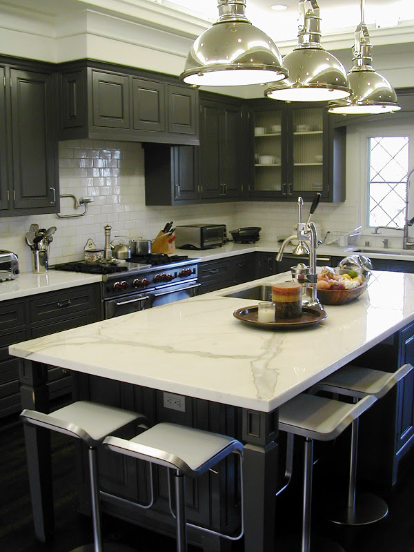 Gourmet kitchen with black cabinets and drawers, nickle pedant lights, white subway tile backsplash, and marble countertop