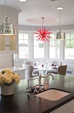 Eat in kitchen with dark countertop and two pendant lights, the breakfast nook has a tulip table and upholstered chairs under a red coral chandelier