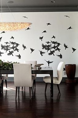 Dining room in a Pacific Palisades home with a mural of a flock of birds, dark wood floor, black table surrounded by white upholstered chairs with wood legs and a chandelier