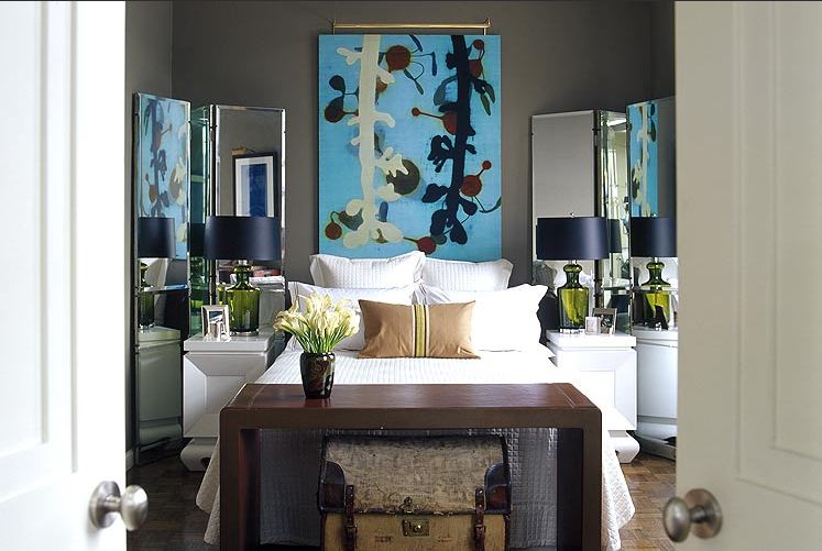 Dark grey bedroom with wood floor, white side tables with mirrored screens behind them, a piece of blue modern art instead of a headboard and a wood table at the foot of the bed with a trunk underneath