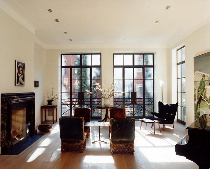 Living room in a New York townhouse with three floor to ceiling paned windows and doors, wood floor, marble fireplace, dueling armchairs, and a grand piano