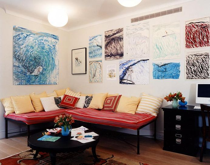 Home office with black desk and white Mac computer, wood floor, walls covered in art, metal sectional daybed with striped red mattress and lots of yellow, white and red pillows and a round black coffee table