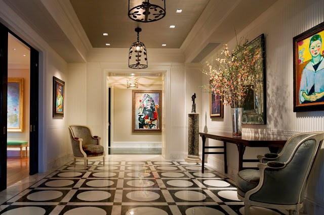 Foyer by Peter Pennoyer with black and white tile floor, white beadboard walls, black pendant lights, and Louis XIV armchairs