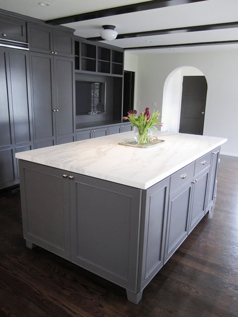 Kitchen with a large grey island topped with Calacatta gold marble, dark wood floor and grey cabinets and drawers