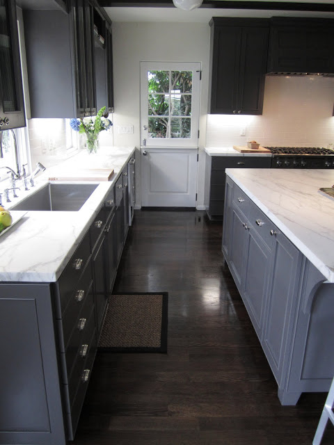 Kitchen with Dutch side door with paned window, grey cabinets and drawers, stained wood floor and marble counter tops