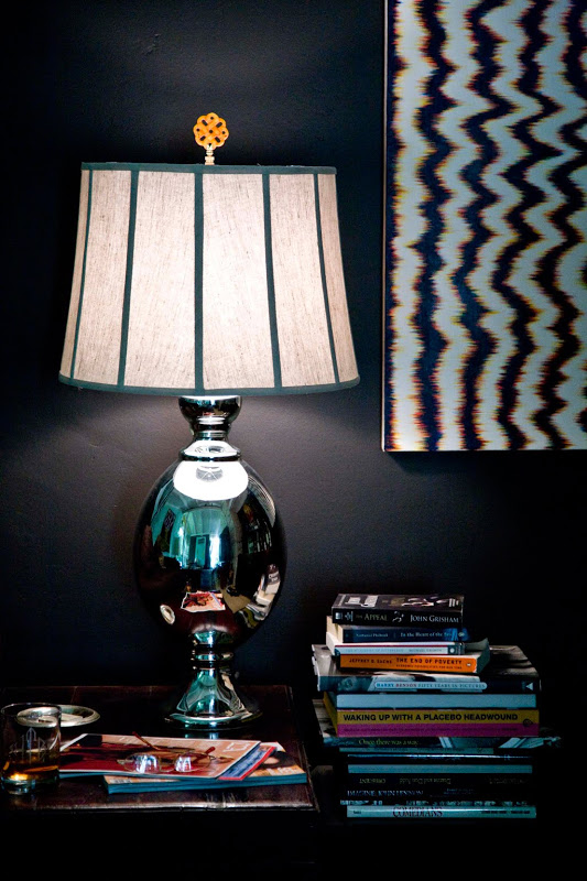 Side table with a polished metal lamp with a gold finial from Hillary Thomas Designs, a stack of books in a room with dark walls and a framed ikat print on the wall