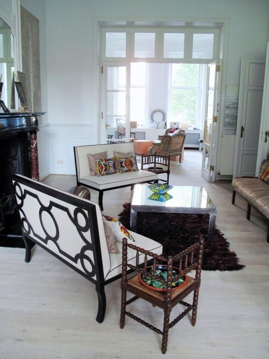 Apartment in Brussels with Casamidy's loop sofa, light wood floor, black fireplace and metal coffee table