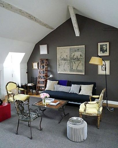Living room in a Paris apartment with dark walls, a wood floor with a large grey area rug, navy sofa, dueling Louis XIV chairs, a metal chair, a coffee table with a wood top and metal legs and a striped stool