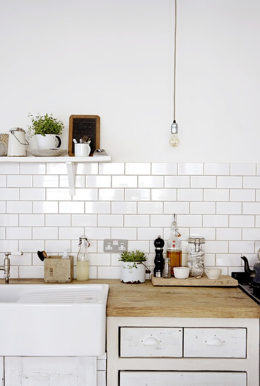 Close up of the exposed bulb lighting, white subway tile backsplash with dark grout lines, and reclaimed butcher block counter tops in a white rustic kitchen.