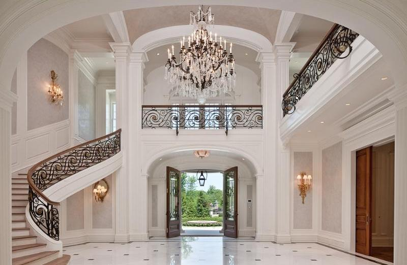 Foyer with black and white tile floor, arched ceiling, crystal chandelier, iron railings and paneled walls
