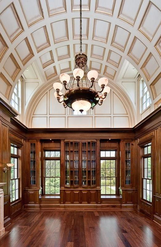 Library with arched, coffered ceiling, chandelier, wood floor and wood paneled walls and cabinets with glass doors