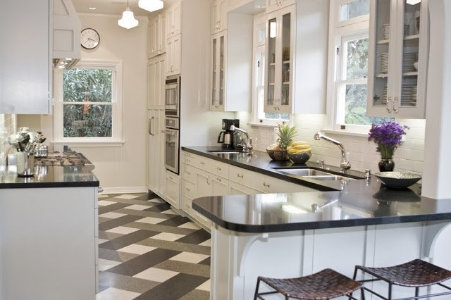 Tom Newman's kitchen in his Los Angeles home with a plaid floor, schoolhouse ceiling lights, stainless appliances, paneled cabinets, black counters and woven barstools