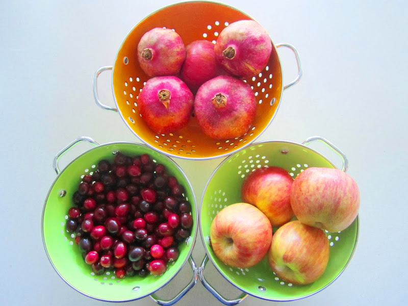 cranberries, pomegranates and apples in colanders on a white table