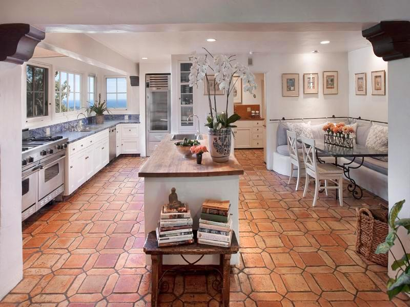 Kitchen in a Montecito mansion with stainless appliances, tile floor, columns, white drawers and cabinets, dark counter tops, an island with a wood counter top and sink and a breakfast nook with banquette seating and a glass table with metal legs