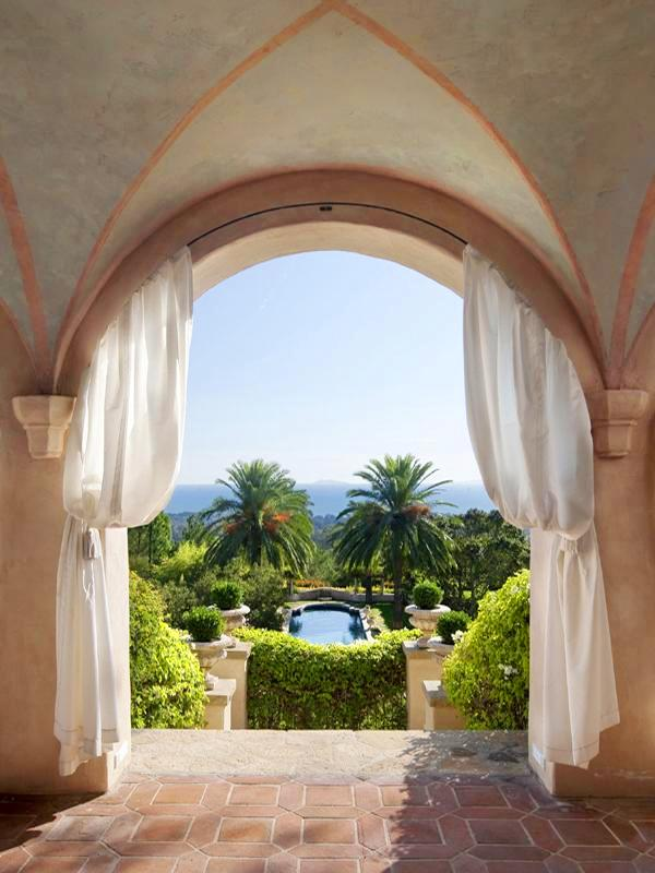 Arched entryway to the backyard of a Montecito mansion with white curtains tied back and saltillo tile floor