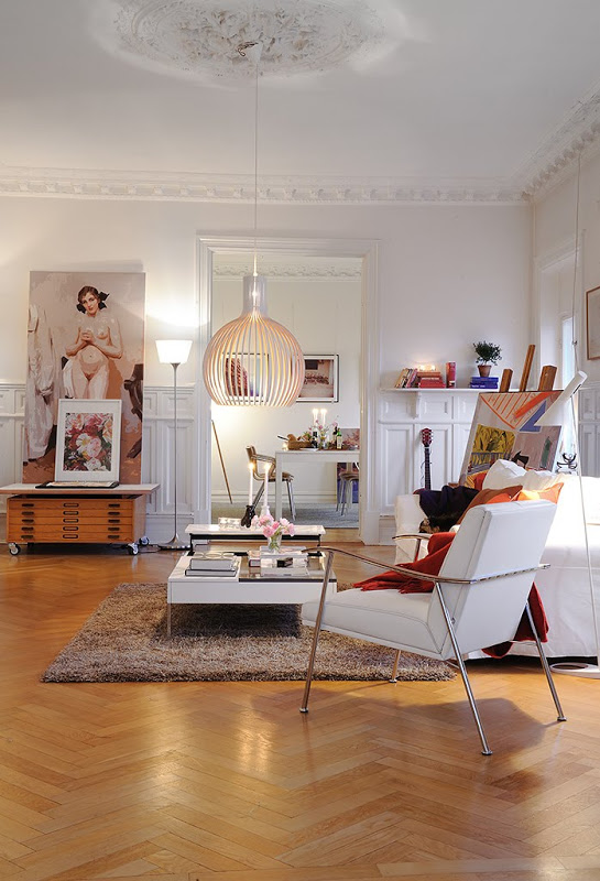 Living room in an apartment in Sweeden with herringbone wood floor, carved crown molding, decorative ceiling medallions, a white sofa with a matching armchair, brown rug, white coffee table, an easel and a brown chest of drawers