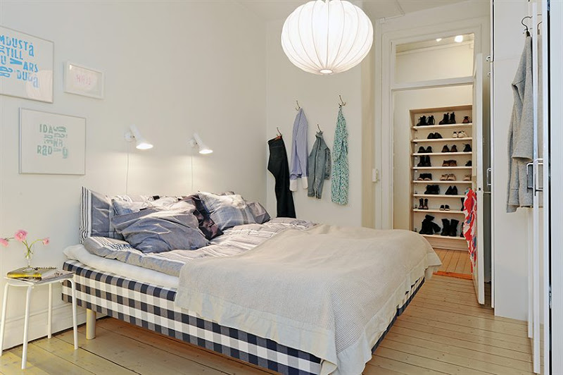 Bedroom with light wood floor, a gingham bed, wall mounted reading light, a bright white lantern and a walk in closet