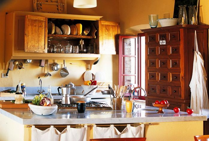 Warm Tuscan kitchen with yellow walls, wood cabinets, a large wooden chest of drawers, and blue grey countertops