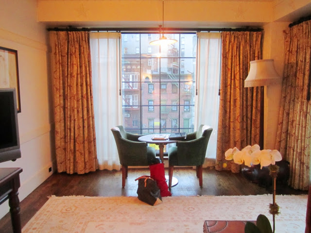 Sitting area in a suite at The Bowery Hotel with two green armchairs around a round table, a floor to ceiling window with a view, wood floor and patterned curtains