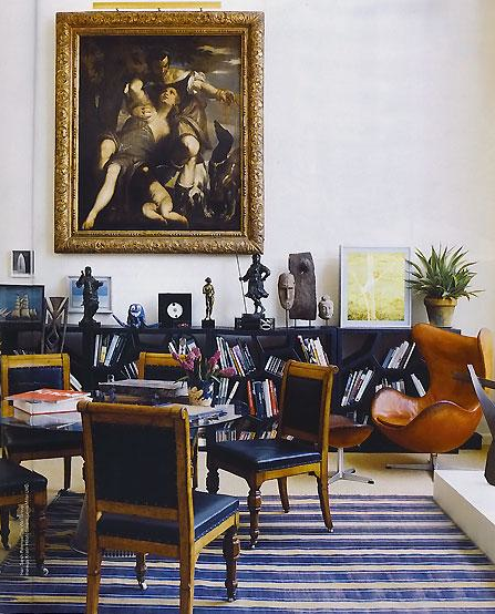 Living room with a round dark wood table, wood chairs with blue leather seats and backs and nail head trim, a blue and cream striped rug, black bookshelf, a tan Egg Chair with matching ottoman and a large classical painting in a gold frame
