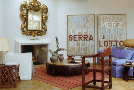 Richard Shapiro's Living room with a white fireplace,a large traditional mirror over the mantel, a striped rug, large, round drum doubling as a coffee table, a blue sofa, white armchair and a wood chair.