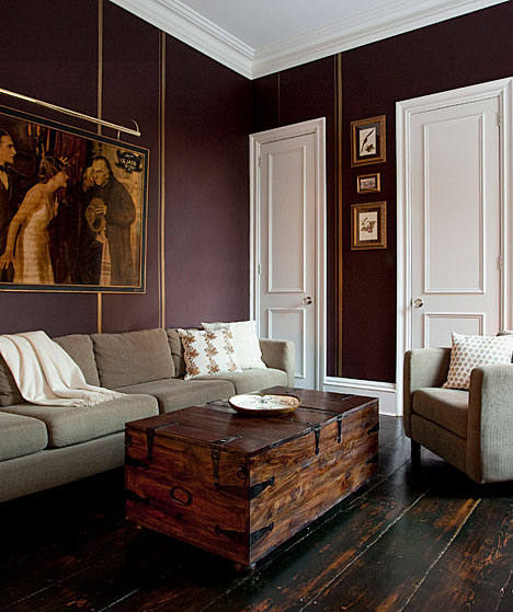 Living room with eggplant walls, gold trim, dark stained wide plank wood floor, a grey sofa with matching armchair and a trunk doubling as a coffee table