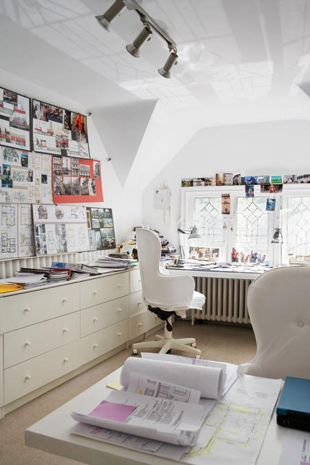 White attic home office with white drawers, two desks with white rolling armchairs,a window and a big bulletin board