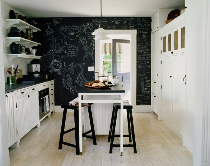 Black and white kitchen with floating shelves, white cabinets and drawers, black counter tops, an island with white legs and a black top surrounded by black stools and a floor to ceiling chalkboard