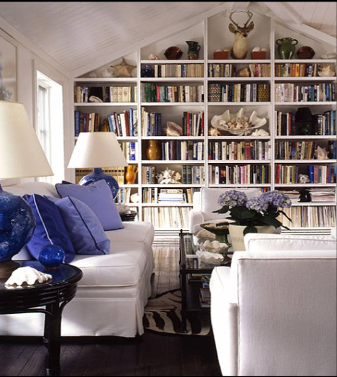 Living room with built in bookshelf full of books, dark wood floor, white sofa and matching armchairs with purple accent pillows, a zebra print rug and two lamps with blue bases and white shades on round dark wood side tables