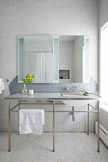 Bathroom with white penny round tile on the walls and floor and a console sinks