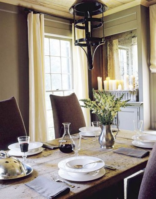 Dining room with raw wood plank ceiling, metal pendant lights, a long wood table surrounded by linen covered Parsons chairs, grey walls, and encasement windows covered by cream curtains