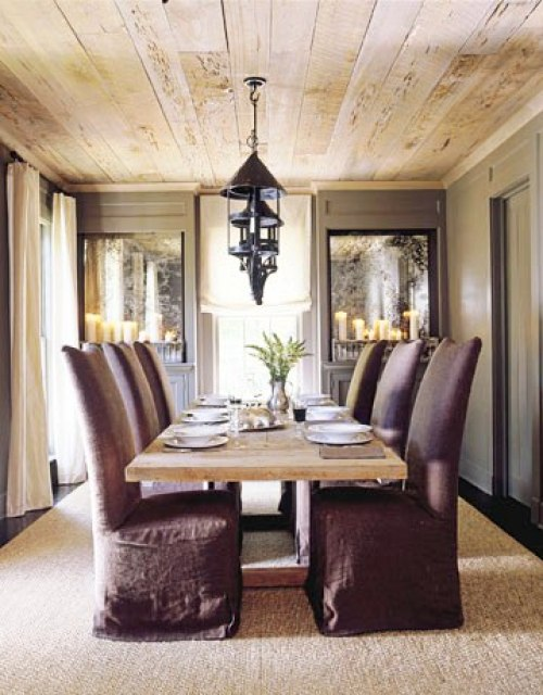 Dining room with raw wood plank ceiling, a row of metal pendant lights, a long wood table surrounded by linen covered Parsons chairs, grey walls, a dark wood floor and a sisal rug