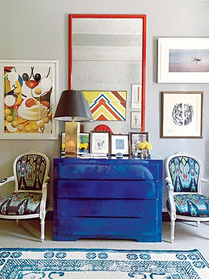 Bedroom with a Yves Klein blue dresser, two ikat print upholstered Louis XIV chairs, a blue and white rug and a large mirror in a red frame
