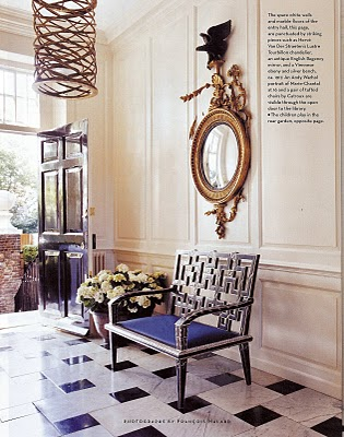 Foyer with black and white marble tile floor, an iron bench with Yves Klein blue cushion, paneled walls and a decorative mirror