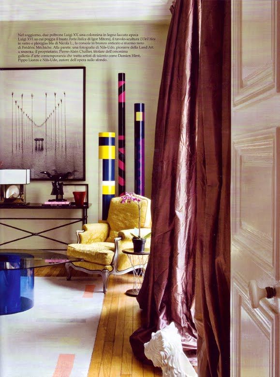 Sitting area with glass coffee table with a a Yves Klein blue base, taffeta curtains and a yellow Louis XIV armchair
