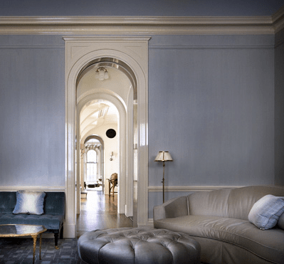 Grey sitting room in a New York brownstone by Peter Pennoyer with arched entryway, grey sofa, blue velvet tufted sofa and a round, grey, tufted ottoman