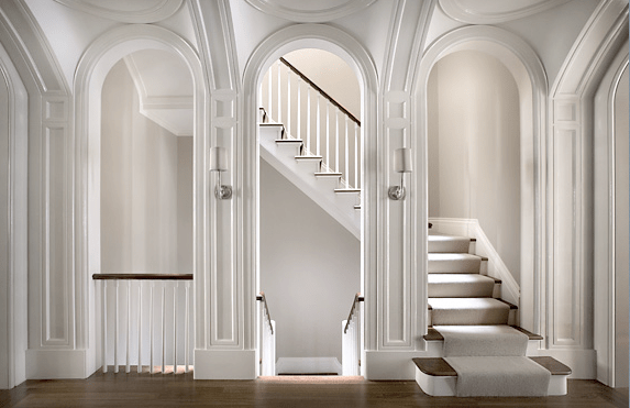 Landing in a New York brownstone with arched entryways by Peter Pennoyer