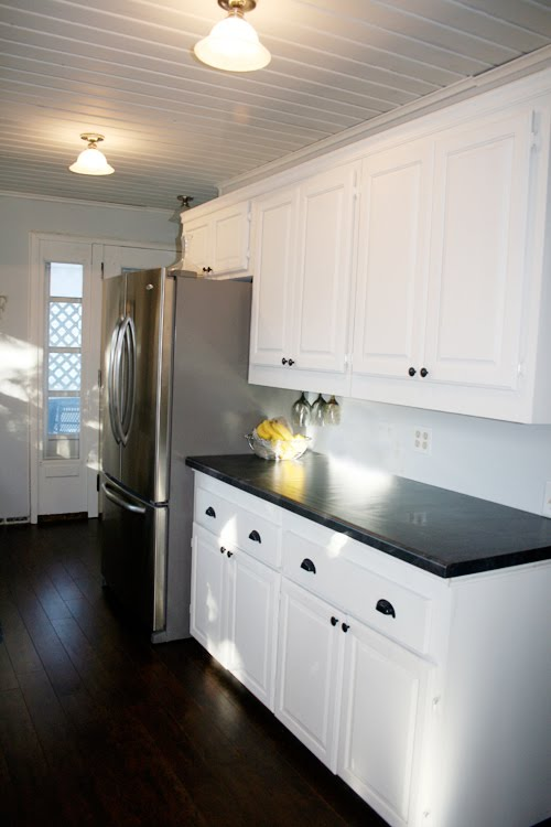 Angela of Fixing it Fancy's kitchen after the remodeling with white cabinets and dark walnut floor