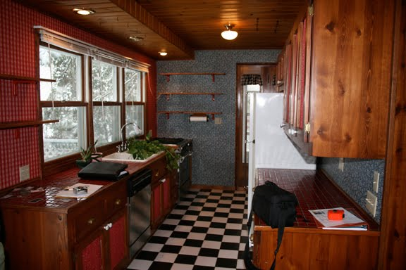 Angela of Fixing it Fancy's kitchen before her remodeling with dark wood cabinets, black and white checker board floor and mismatched wallpaper