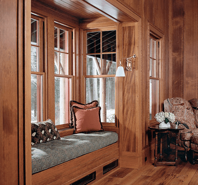 Window seat in a bay window in a living room by Peter Pennoyer