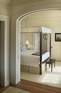 Cream colored bedroom with a wood four poster bed by Peter Pennoyer