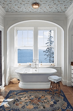 Master bathroom in an arched nook by Peter Pennoyer with a stand alone tub, view of the sea and a wallpapered ceiling