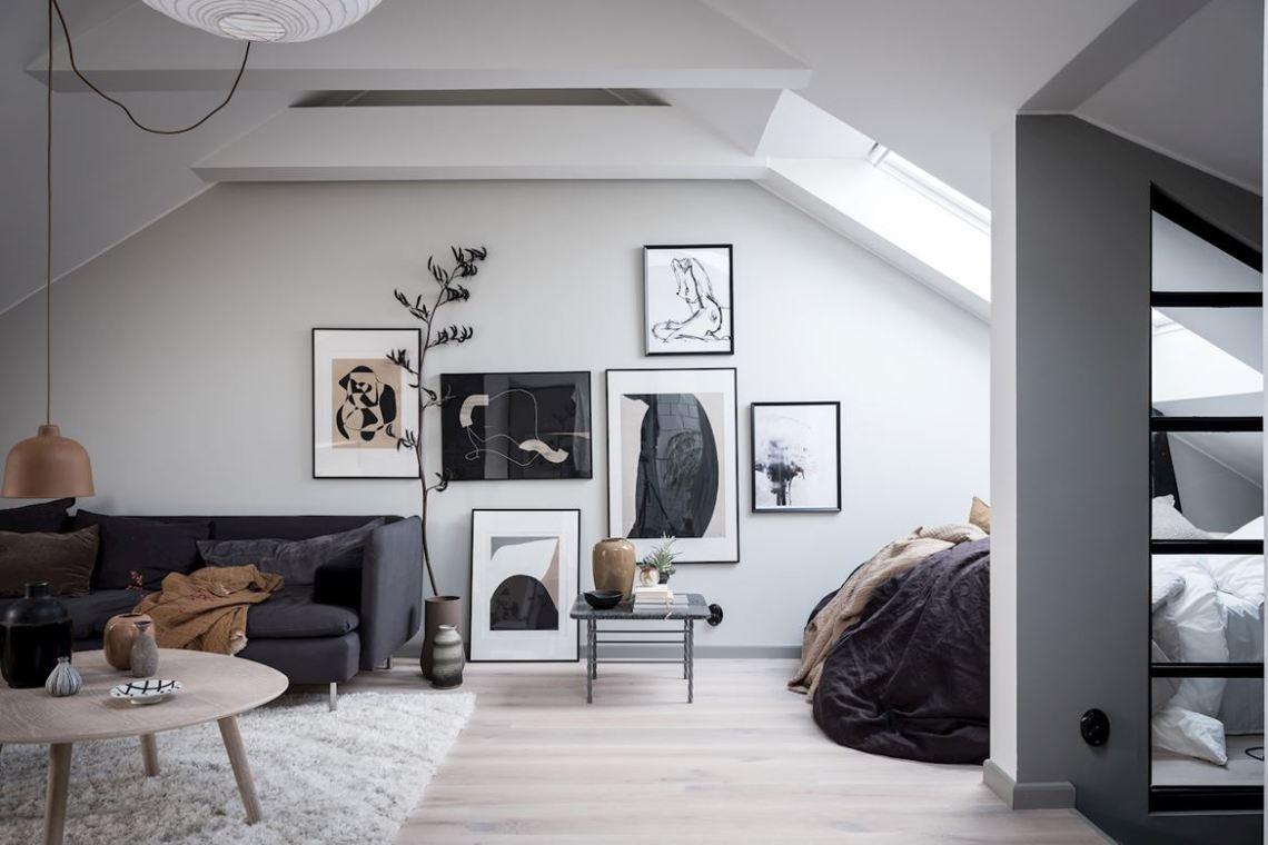 Simple modern room with asymmetrical gallery wall hanging and leaning against wall