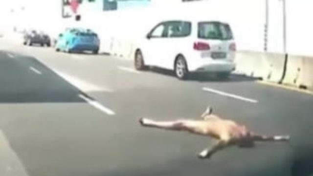 Screengrab of the video of a naked man lying on the road yesterday. Photo: ROADS.sg/Facebook