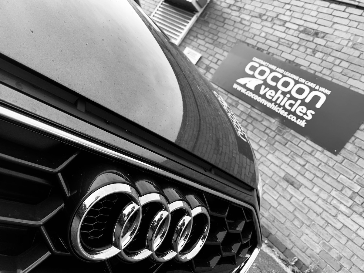 Audi in Black and White with Cocoon Sign in back